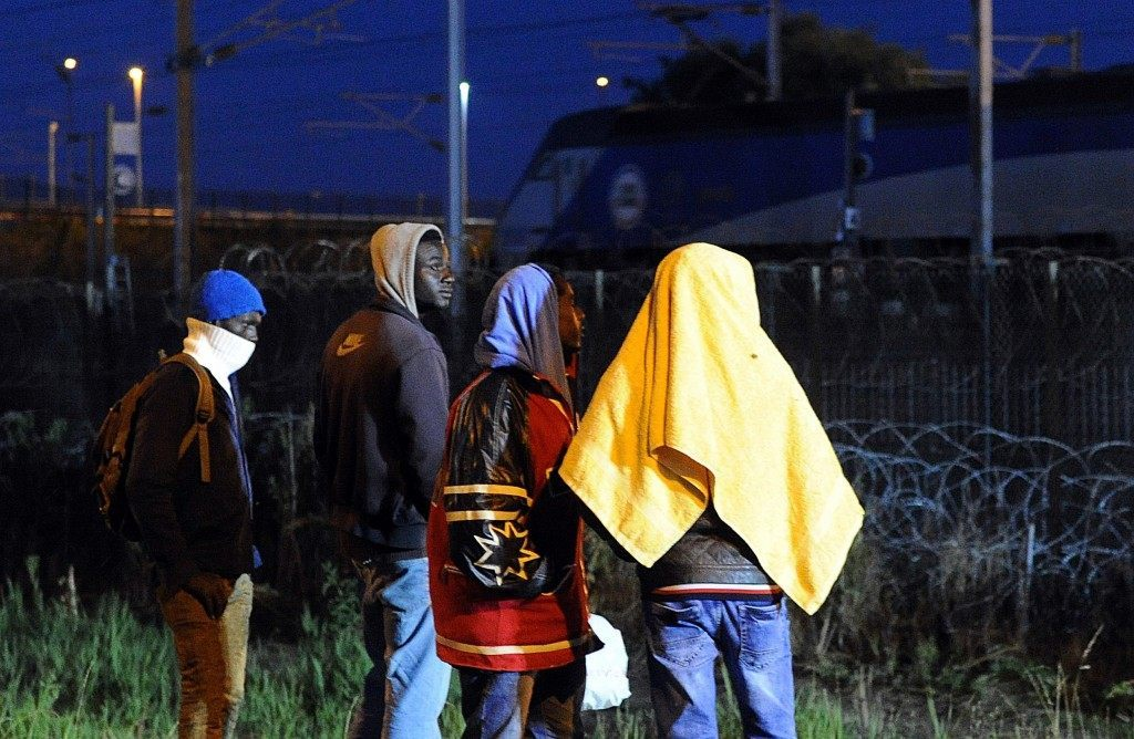 Migrants walk in the proximity of the Eurotunnel rail terminal in Coquelles (FRANCOIS LO PRESTI/AFP/Getty Images)