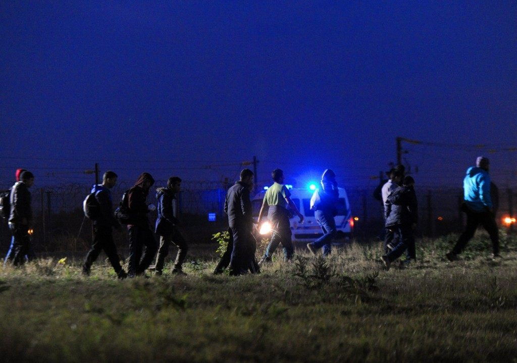 Migrants walk in the proximity of the Eurotunnel rail terminal (FRANCOIS LO PRESTI/AFP/Getty Images)