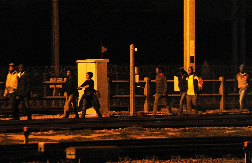 Migrants walk along the railway tracks of the Eurotunnel terminal (FRANCOIS LO PRESTI/AFP/Getty Images)