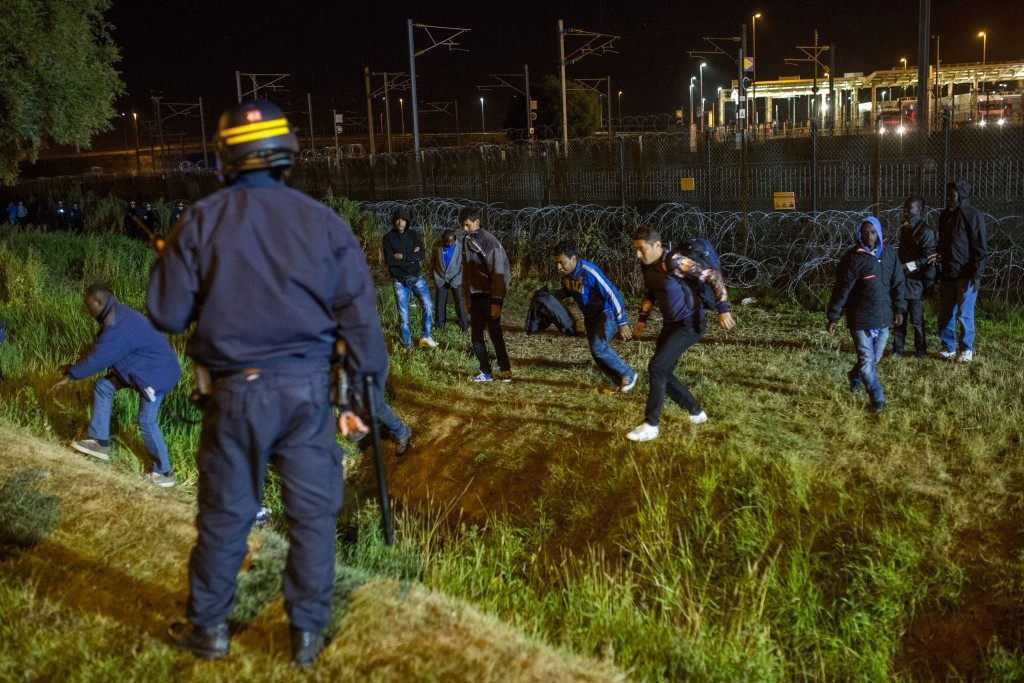 A policeman watches men move away from a security fence beside train tracks (Rob Stothard/Getty Images)