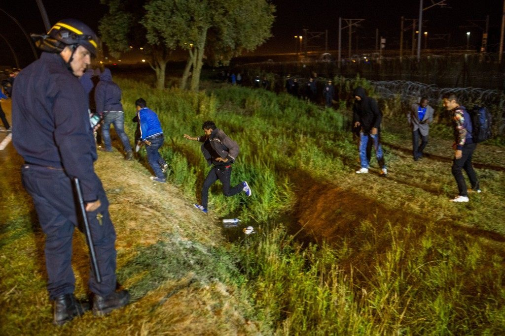 A policeman watches men move away from a security fence beside train tracks near the Eurotunnel terminal (Rob Stothard/Getty Images)