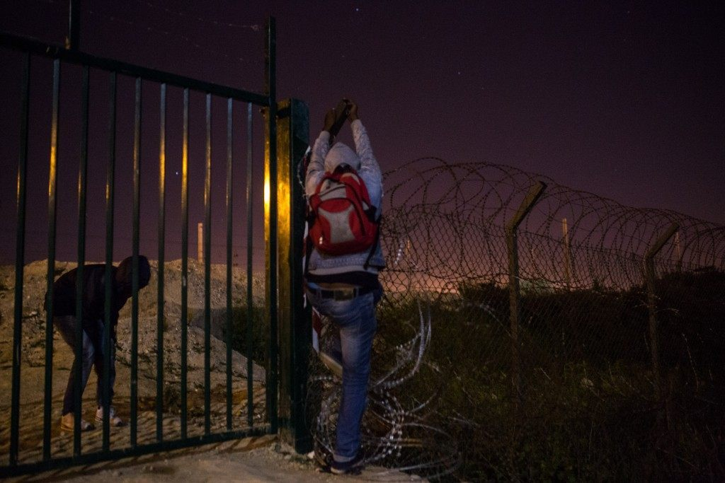 A man attempts to climb a security fence (Rob Stothard/Getty Images)
