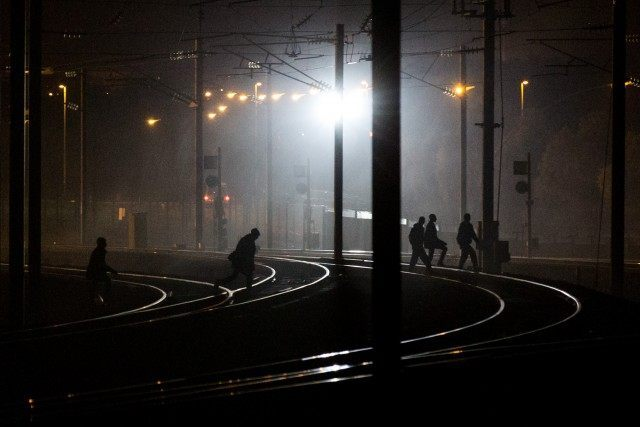 People walk across train tracks near the Eurotunnel terminal (Rob Stothard/Getty Images)