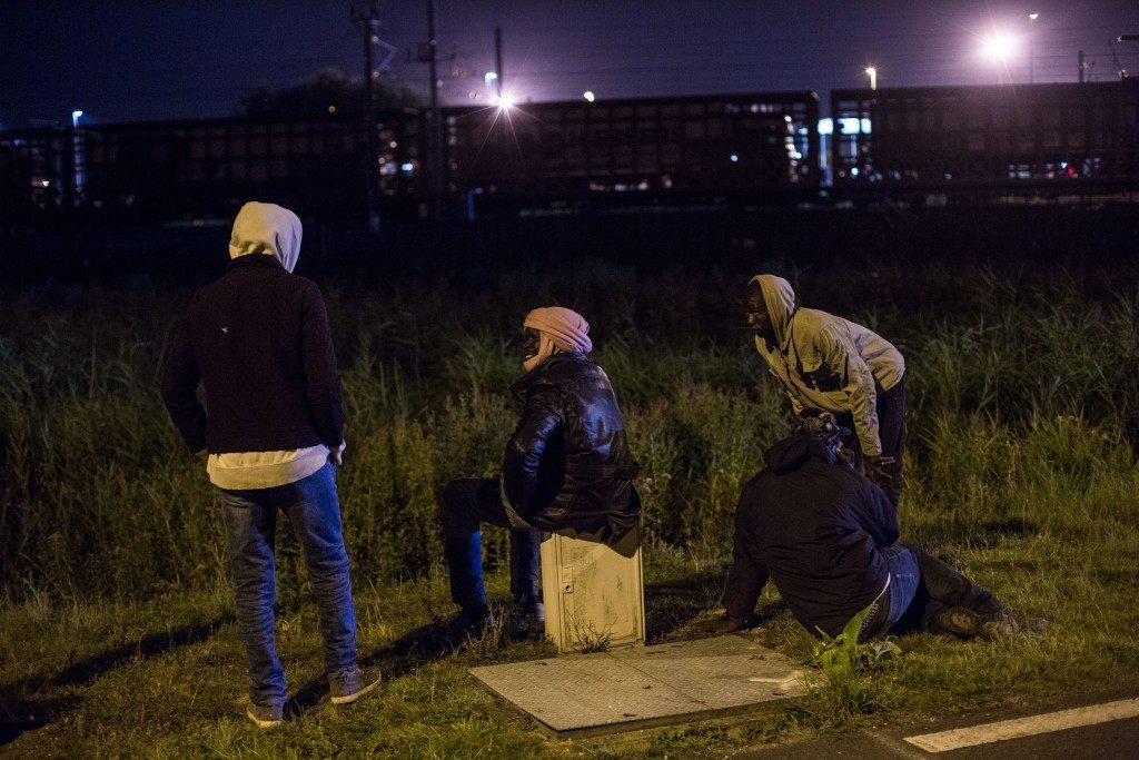 Men watch a train transporting trucks arrive at the Eurotunnel terminal (Rob Stothard/Getty Images)