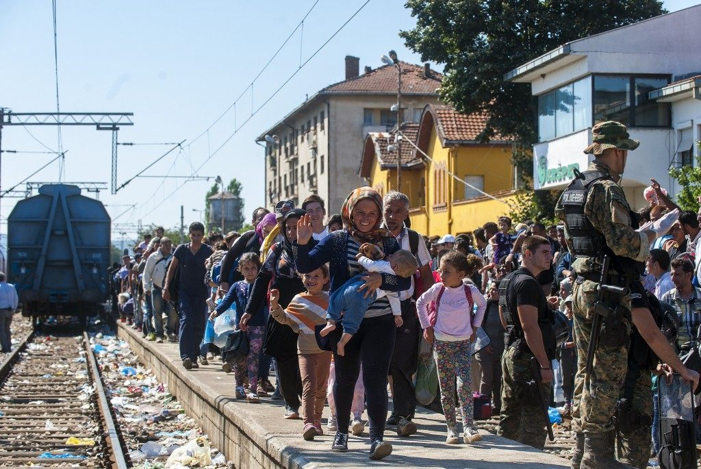 Migrants walk on a platform at the train station in the town of Gevgelija, on the Macedonian-Greek border, as they try to board trains to Serbia (ROBERT ATANASOVSKI/AFP/Getty Images)