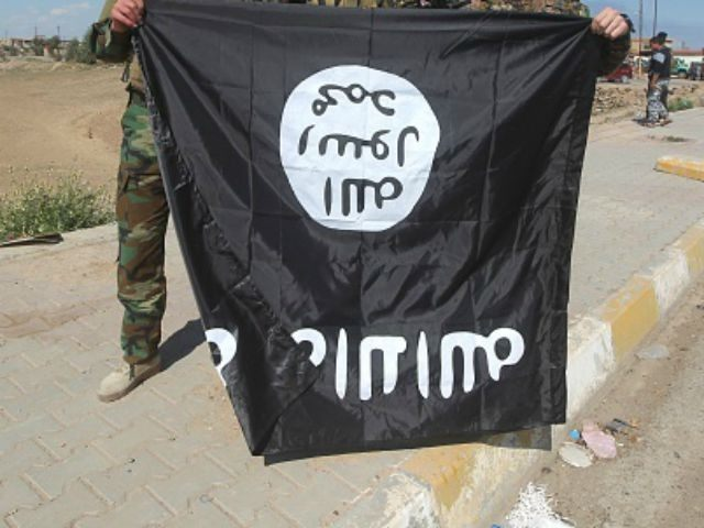 raqi Sunni and Shiite fighters pose for a photo with an Islamic State (IS) group flag in the Al-Alam town, northeast of the Iraqi city of Tikrit, on March 17, 2015 after recapturing the town from IS fighters earlier in the month. Loyalists had already failed three times to retake …