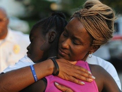 Sergeant Dominica Fuller consoles a mourning child during a candlelight vigil held in honor of Jamyla Bolden on August 20, 2015 in Ferguson, Missouri. Jamyla Bolden, 9, was allegedly struck by a stray bullet from a drive-by shooting and killed while doing her homework at her home in Ferguson on August 18th. (Photo by