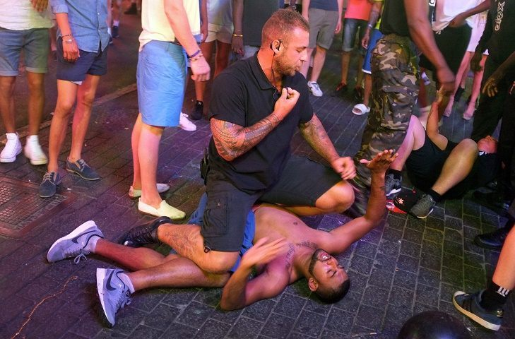 A security guard subdues a man at Punta Ballena street in Magaluf / AFP PHOTO / JAIME REINA