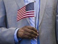 A man holds an US flag prior to taking the citizenship oath to become a US citizen during a naturalization ceremony at the US Patent and Trademark Office in Alexandria, Virginia, May 28, 2015. AFP PHOTO / SAUL LOEB (Photo credit should read