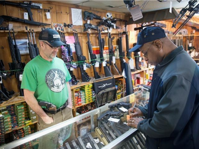 UNITED STATES, Tinley Park : TINLEY PARK, IL - MARCH 11: Danny Egan (L) helps a customer shop for a handgun at Freddie Bear Sports on March 11, 2015 in Tinley Park, Illinois. According to a survey conducted by the University of Chicago 32 percent of Americans own guns, down …