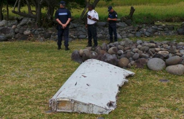 French gendarmes and police stand near a large piece of plane debris which was found on the beach in Saint-Andre, on the French Indian Ocean island of La Reunion