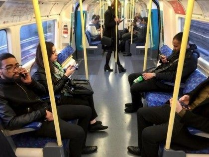 Commuters use their mobile devices on an underground tube train in London