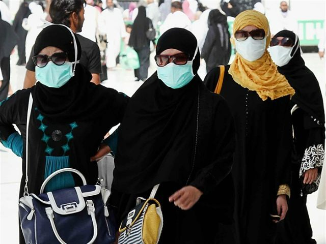 SAUDI ARABIA, MECCA : TO GO WITH AFP STORY BY ABDEL HADI HABTOOR Muslim pilgrims wear nose and mouth masks on the way to Islam's holiest shrine, the Kaaba, in the Grand Mosque in the Muslim holy city of Mecca in Saudi Arabia on May 27, 2014. Muslims pilgrims from …