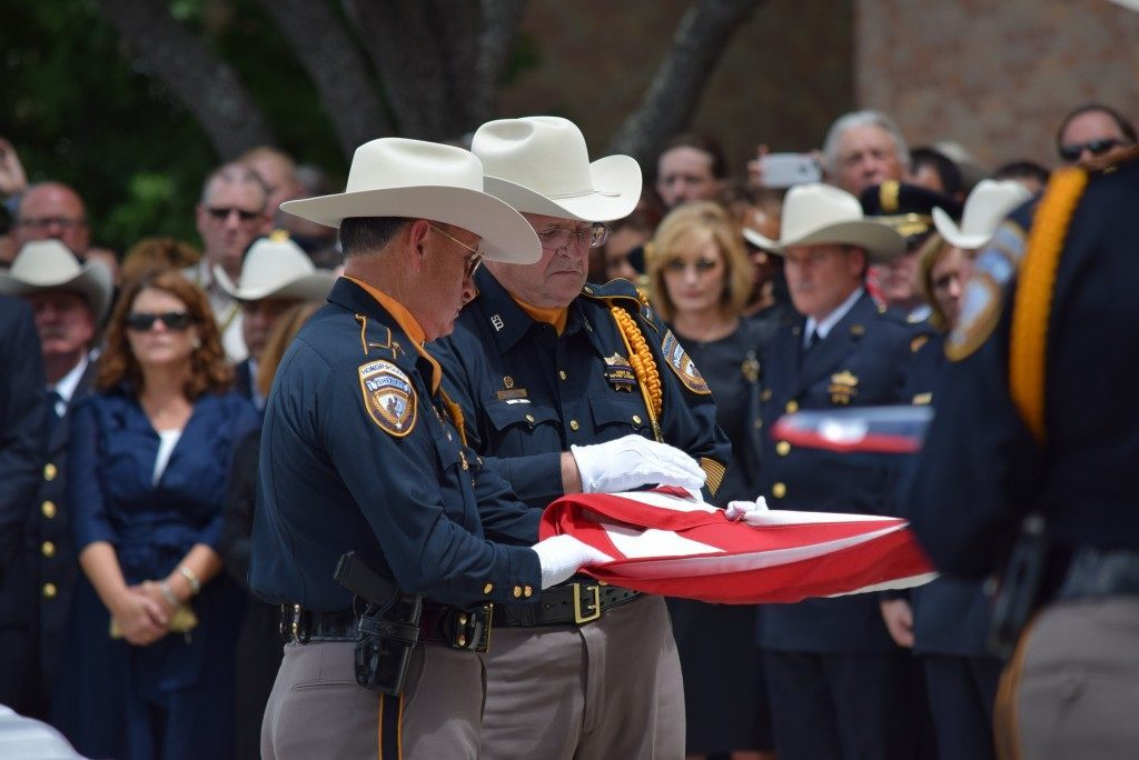 Honor Guard members fold the U.S. flag that covered Darren Goforth's casket.