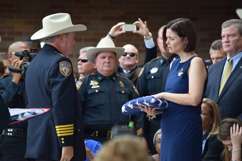 Sheriff Ron Hickman presents the flag to Kathleen Goforth.