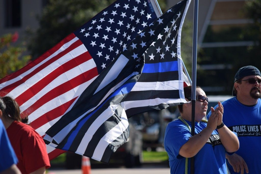 "Carrying the American and ""Thin Blue Line"" flags during the #PoliceLivesMatter march in Houston. (Photo: Breitbart Texas/Bob Price)"
