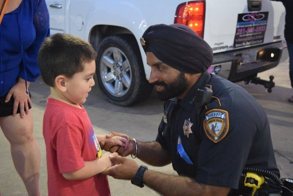 Harris County Sheriff's Deputy Sandeep Dhaliwal  talks with a young boy about Deputy Goforth. (Photo: Breitbart Texas/Bob Price)