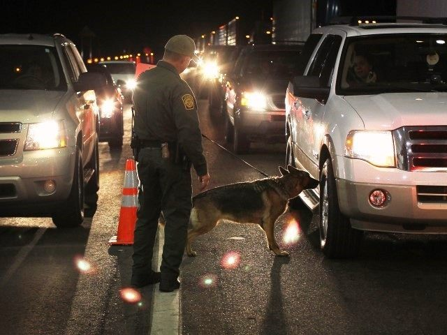 Caption:NOGALES, AZ - DECEMBER 07: A border patrol agent and Gitta, a drug-sniffing German shepherd, work a checkpoint on December 7, 2010 north of Nogales, Arizona. The checkpoint falls in the Tucson sector of the U.S.- Mexico border and is considered the most heavily trafficked by illegal immigrants and drug smugglers in the United States. (Photo by John Moore/Getty Images)