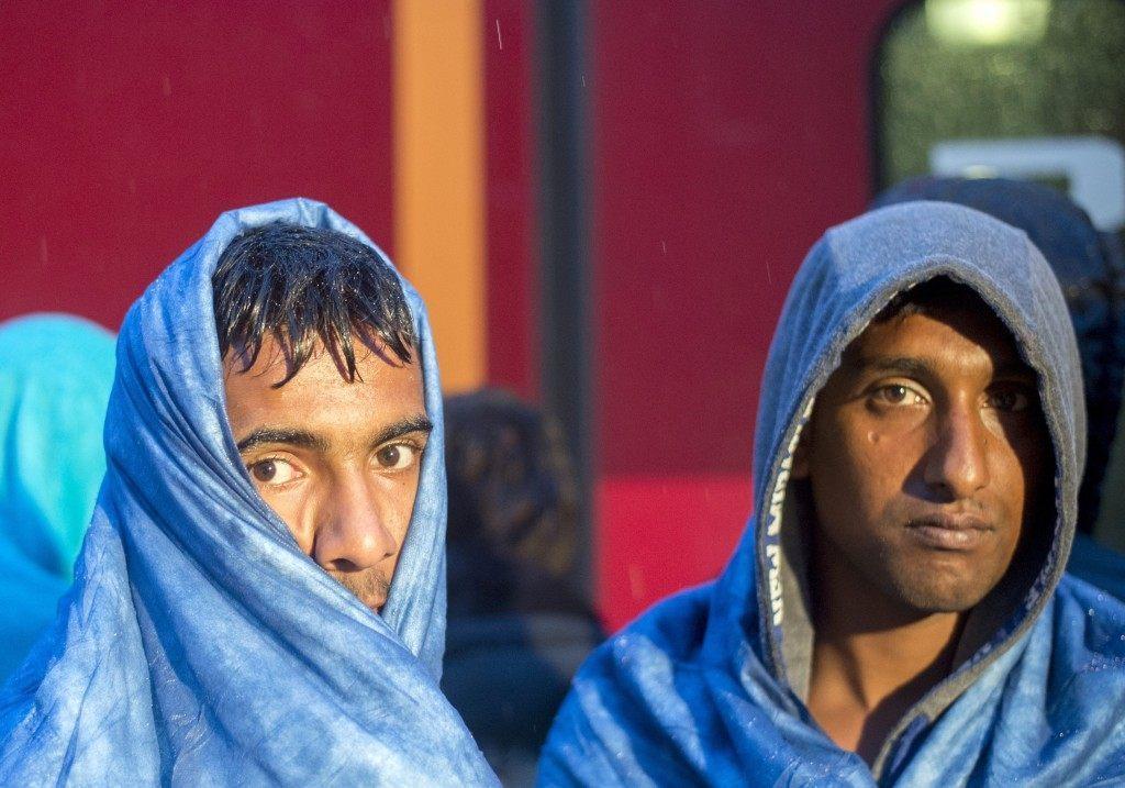 Migrants look on before boarding a train in the village of Nickelsdorf (JOE KLAMAR/AFP/Getty Images)