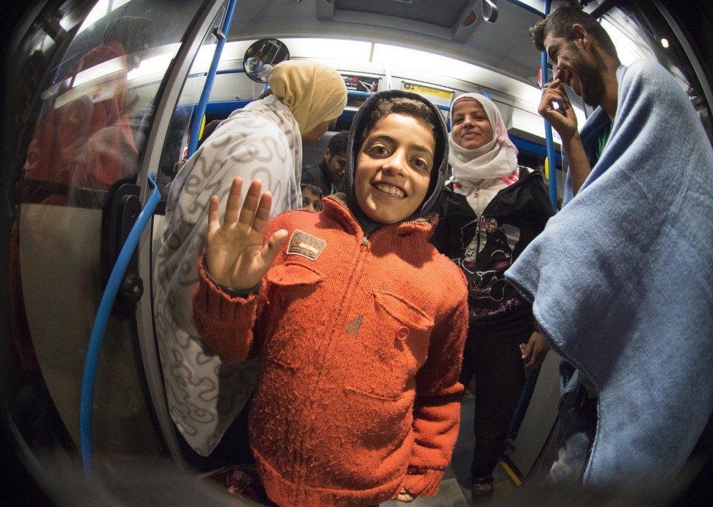 Migrants smile standing in a bus upon arrival at the village of Nickelsdorf (JOE KLAMAR/AFP/Getty Images)