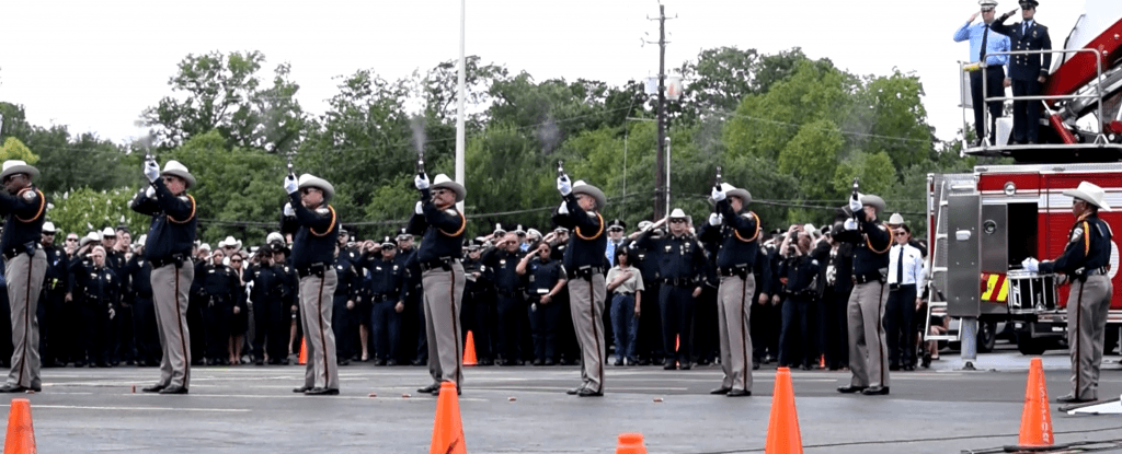 Harris County Sheriff's Honor Guard fires a 21-gun salute.