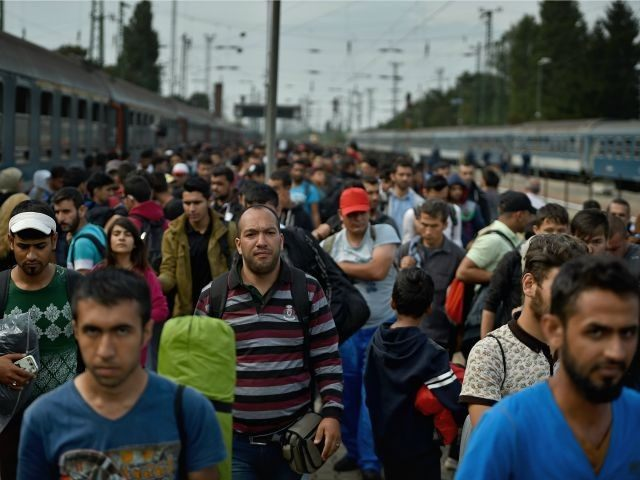 HEGYSHALOM, HUNGARY - SEPTEMBER 15: Hundreds of migrants arrive off a train from Roszke, at Hegyshalom railway station on the Austrian border after Hungarian authorities closed the open railway track crossing on September 15, 2015 in Hegyeshalom, Hungary.