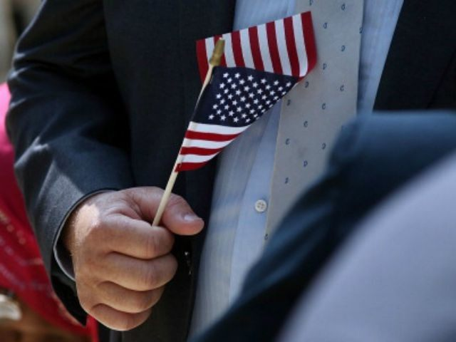 A man holds an American Flag before taking the Oath of Allegiance during a special naturalization ceremony at the Metropolitan Museum of Art on July 22, 2014 in New York City. Over fifty people representing countries from Albania to Burundi took part in the morning ceremony at the American Wing …