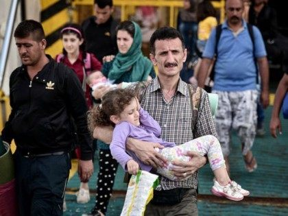 A Syrian family disembarks from the Greek government chartered Eleftherios Venizelos ferry at the port of Piraeus on September 9, 2015. Thousands of refugees arrived in Piraeus by goverment chartered ferry from the overcrowded Greek islands, especially the island of Lesbos. EU Commission chief Jean-Claude Juncker unveiled major plans Wednesday …