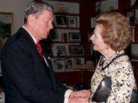 Former US President Ronald Reagan (L) shakes hands