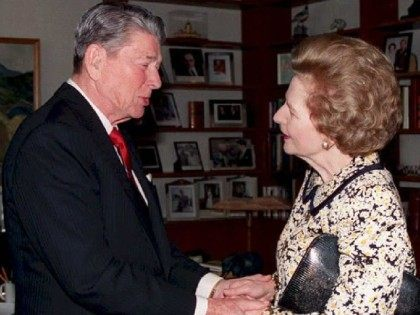 Former US President Ronald Reagan (L) shakes hands