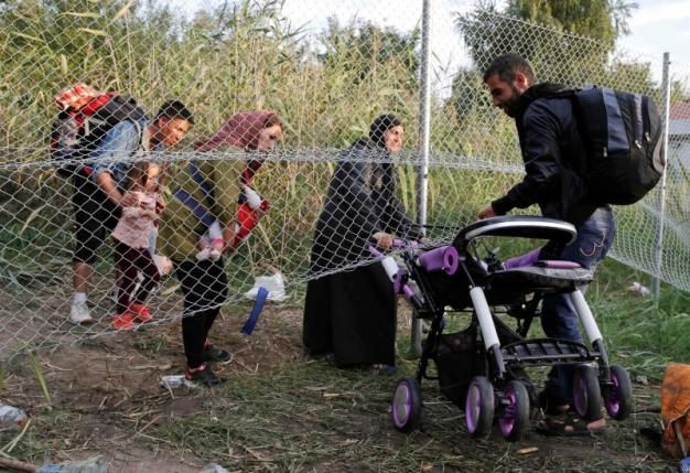 Migrants pass under highway security fence as they try to find a new way to enter Hungary after Hungarian police sealed the border with Serbia near the village of Horgos