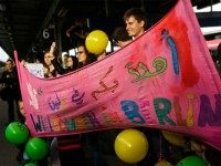 SCHOENEFELD, GERMANY - SEPTEMBER 13: People hold a banner to welcome migrants arriving on an ICE high-speed train of Deutsche Bahn from Munich near Berlin on September 13, 2015 in Schoenefeld, Germany.