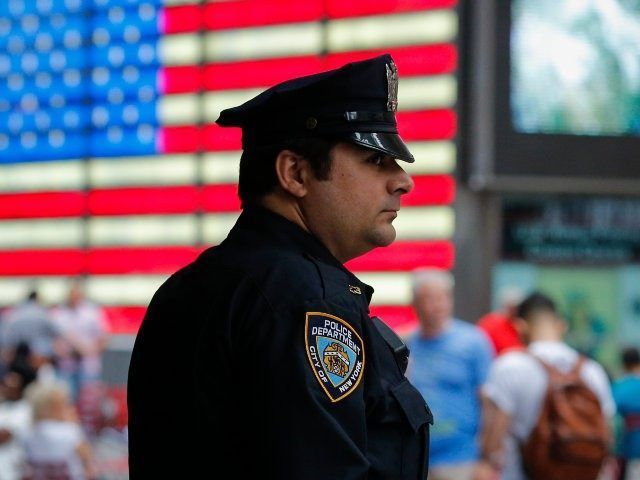 New York Police Officer keeps an eye on tourist as he stands guard at Times Square on July 4, 2015 in New York City. Security was heightened with more than 7.000 NYPD officers at landmark places and crowded streets after that the Federal Bureau of Investigation and the Department of …