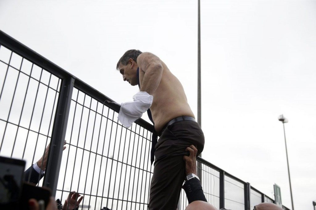 Air France Executive Vice President in charge of Human Resources and Labour Relations Xavier Broseta, shirtless, tries to cross a fence, helped by security and police officers.  (KENZO TRIBOUILLARD/AFP/Getty Images)
