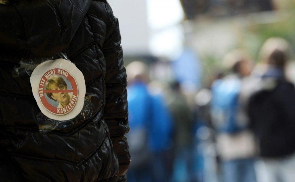 """""""Merkel is Not My Chancellor"""" Reads A Badge Worn by a Protester"""