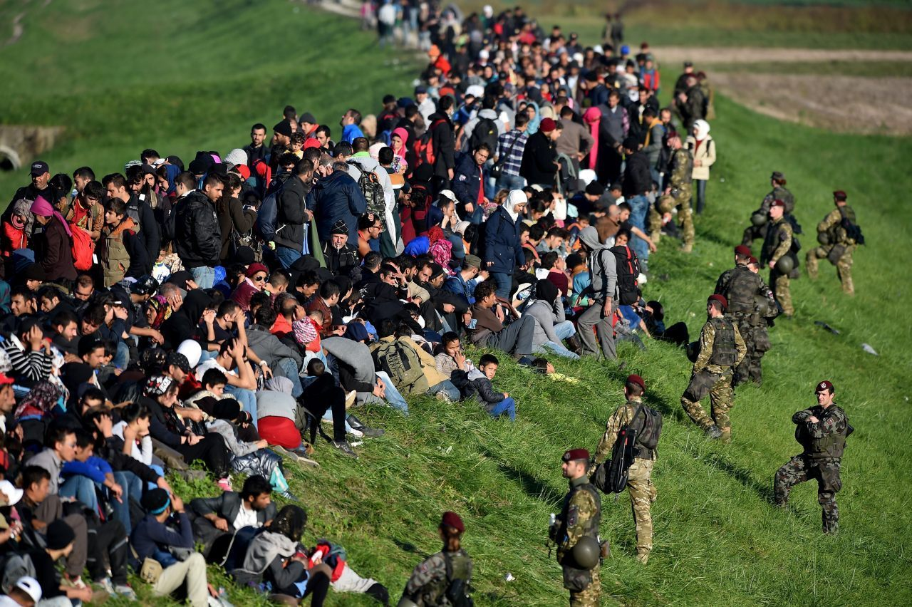 Migrants are escorted through fields by police and the army (Photo by Jeff J Mitchell/Getty Images)