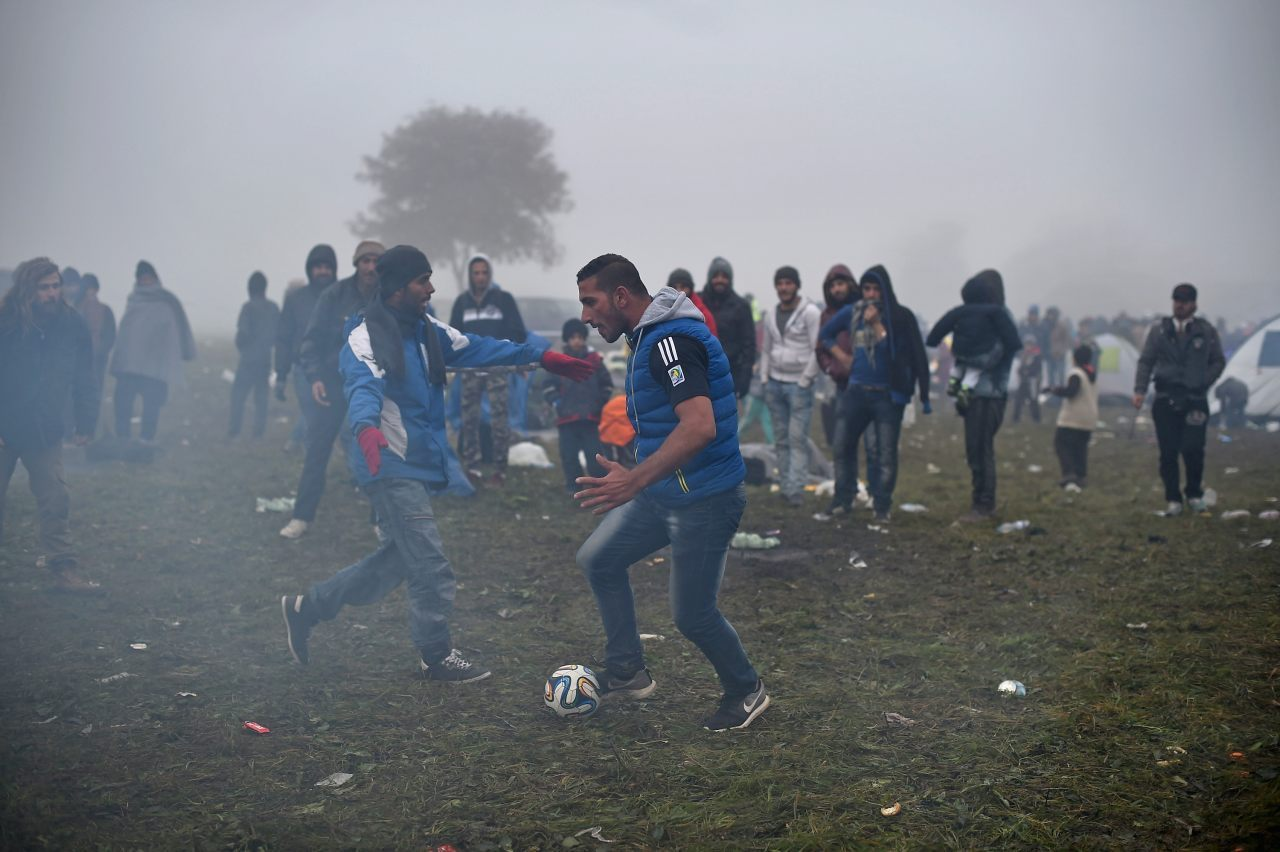 Migrants play football while they are held back by the police near the village of Rigonce (Photo by Jeff J Mitchell/Getty Images)