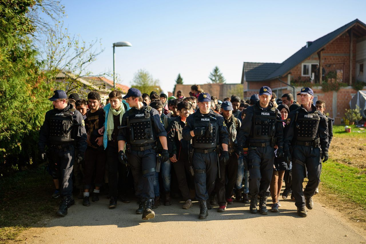 Police escort migrants and asylum seekers as they walk to a refugee centre after crossing the Croatian-Slovenian border (Makovec/AFP/Getty Images)
