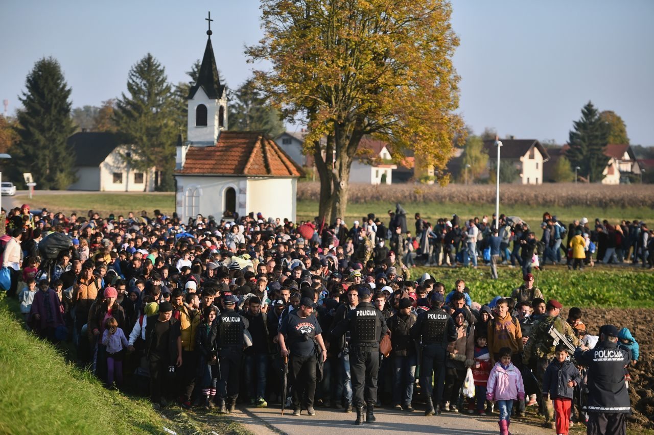 Migrants and refugees, who spent the night outdoors, are escorted by Slovenian soldiers and police officers AFP PHOTO STRINGER
