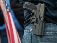 OLYMPIA, WA - JANUARY 19: A demonstrator carries a handgun while listening to speakers at a pro-gun rally on January 19, 2013 in Olympia, Washington. The Guns Across America campaign drew thousands to state capitals, including over 1,000 demonstrators in Olympia. (Photo by David Ryder/Getty Images)