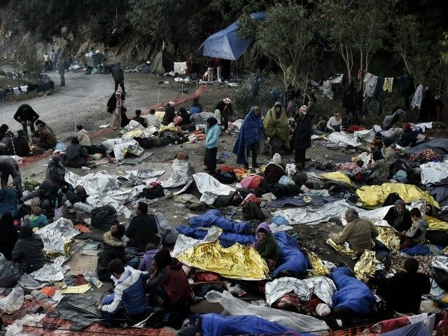 A photo taken on October 5, 2015 shows refugees and migrants a day after they spent a night in a field on the Greek island of Lesbos after crossing the Aegean sea from Turkey on October 5, 2015.