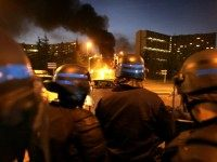 Policemen stand guard as a bus is burning at the entrance of 'Le Mirail', a sensitive neighbourghood of Toulouse, west southern France, 07 November 2005.