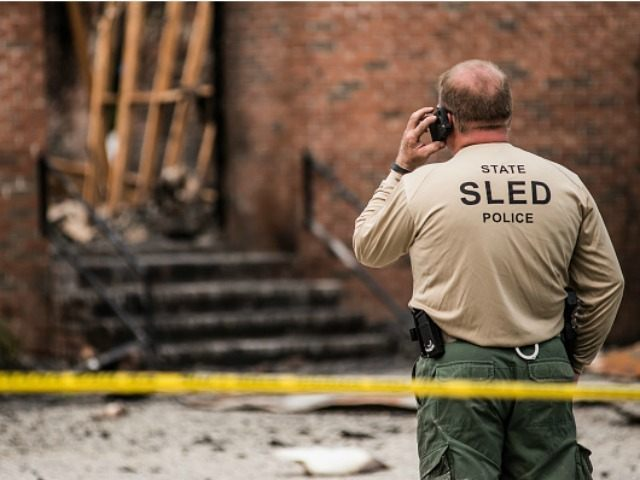 An Investigator with the State Police examines the burned ruins of the Mt. Zion AME Church July 1, 2015 in Greeleyville, South Carolina. Federal and state agencies are investigating a recent string of church fires in the South that have occured since the church massacre in nearby Charleston, South Carolina. …