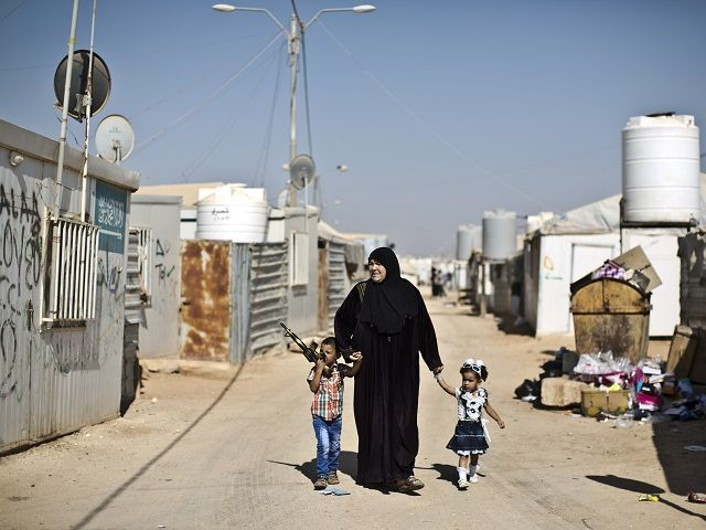 Syrian refugee children dressed in new clothes hold the hands of their grandmother while walking back to their shelter on the first day of the Eid al-Fitr holiday that marks the end of the holy fasting month of Ramadan at Zaatari refugee camp, in Mafraq, Jordan, Friday, July 17, 2015. (AP Photo/Muhammed Muheisen)