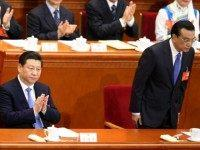 China's President Xi Jinping (L) claps as Premier Li Keqiang (R) bowing at the beginning of the opening session of the National People's Congress (NPC) at the Great Hall of the People on March 5, 2014 in Beijing, China. China plans to raise defense budget by 12.2 percent to 808.2 …