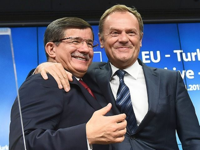 Turkish Prime Minister Ahmet Davutoglu (L) hugs European Council president Donald Tusk during a press conference at the end of a summit on relations between the European Union and Turkey and on the migration crisis at the European Council in Brussels on November 29, 2015. AFP PHOTO / EMMANUEL DUNAND …