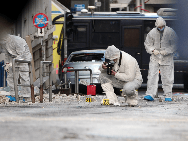 Police forensic experts search for evidence outside the Greece's industry association offices in Athens, after a bomb exploded on early November 24, 2015.