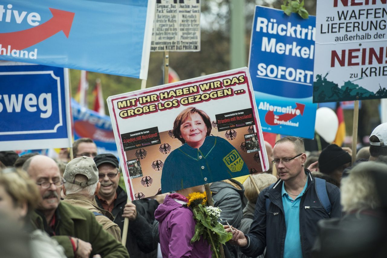 "An AfD supporter holds a placard depicting Angela Merkel wearing the uniform of the old Communist ""German Free Youth"". The text says: ""With her we have hit the jackpot..."" (JOHN MACDOUGALL/AFP/Getty Image)"
