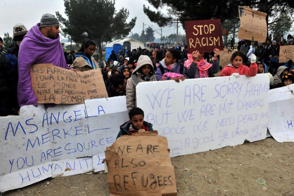 Migrants and refugees hold a placard (C) reading 'We are sorry France' refering to the Paris attacks as they wait to cross the border between Greece and Macedonia near the Greek village of Idomeni on November 21, 2015. Serbia and Macedonia, which lie on the main migrant route to northern Europe, have begun restricting the entry of refugees to just those from certain countries, the UN refugee agency said on November 19. AFP PHOTO /SAKIS MITROLIDIS (Photo credit should read SAKIS MITROLIDIS/AFP/Getty Images)