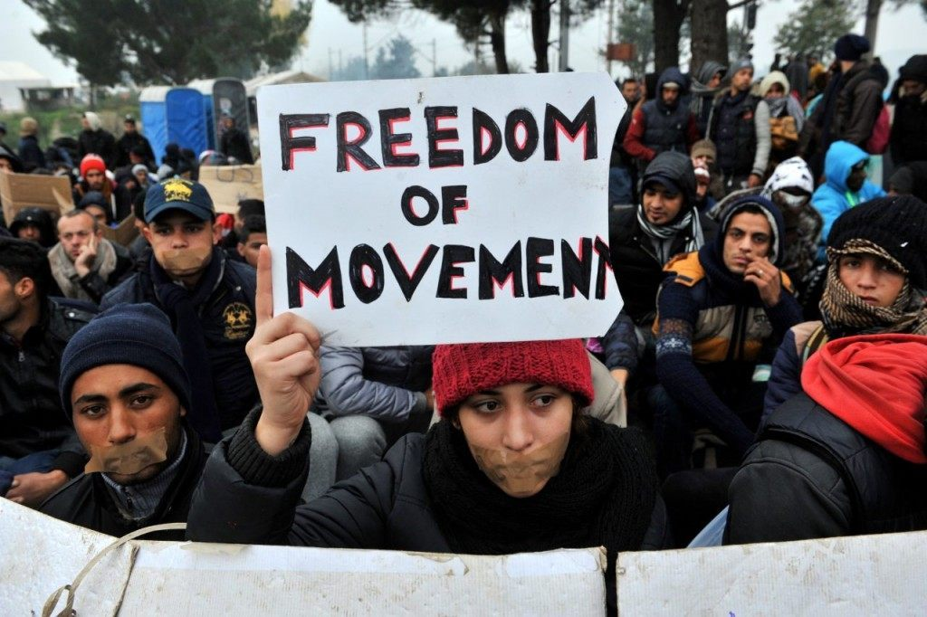 A migrant holds a placard (C) reading 'Freedom of movment' as she waits to cross the border between Greece and Macedonia near the Greek village of Idomeni on November 21, 2015. Serbia and Macedonia, which lie on the main migrant route to northern Europe, have begun restricting the entry of refugees to just those from certain countries, the UN refugee agency said on November 19. AFP PHOTO /SAKIS MITROLIDIS (Photo credit should read SAKIS MITROLIDIS/AFP/Getty Images)